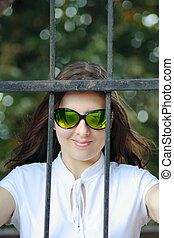 The young woman in sun glasses behind an iron protection
