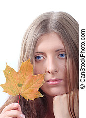 The thoughtful girl with maple autumn sheet
