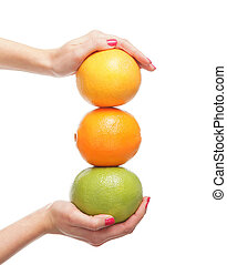 Beautiful female hands with the fruits isolated on white