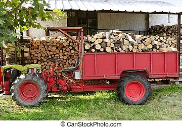 Firewood tractor in red color with stacked wood