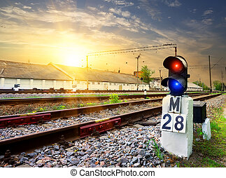 Railway semaphore near industrial station at sunset