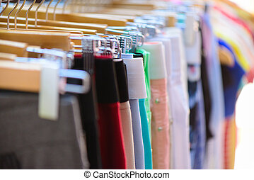 Variety of clothes hanging on rack in boutique