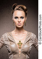 Young, beautiful and rich woman in jewels of gold and stones...