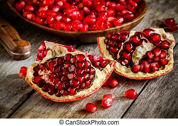 Ruby pomegranate open with seeds closeup on wooden table -...