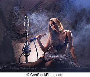 Young sexy woman in luxury underwear smoking the hookah in...