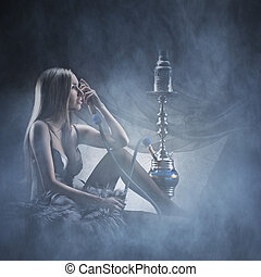 Beautiful girl in sexy underwear smoking the hookah