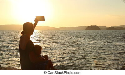 mother makes selfy  with daughter against backlight at sunset
