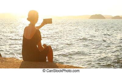 young blonde woman makes selfy at sunset against back light