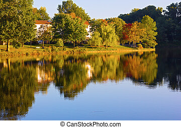 Autumn in a front lake community of Northern Virginia, US. Picturesque residential neighborhood with colorful trees in the fall.