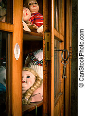 Slightly opened glass cabinet with antique dolls