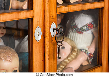 Locked glass cabinet with antique dolls