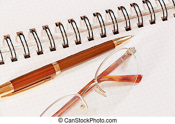 Pen, notebook and glasses on office desk