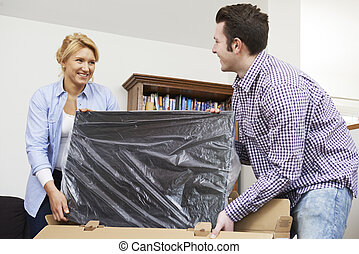 Couple Unpacking New Television At Home