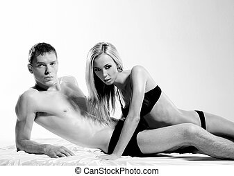 Black and white portrait of young sexy couple over white...