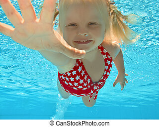 Child swimming underwater in pool - Happy young girl...