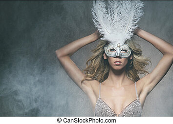 Portrait of young beautiful woman in mask