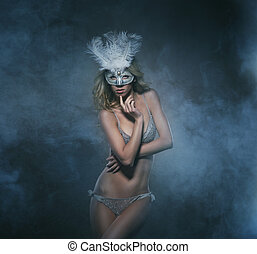 Young sexy woman in erotic lingerie and mask over the luxury bac