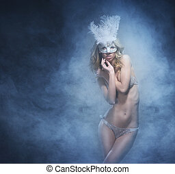 Beautiful and sexy striptease dancer in lingerie and mask over the smoky background
