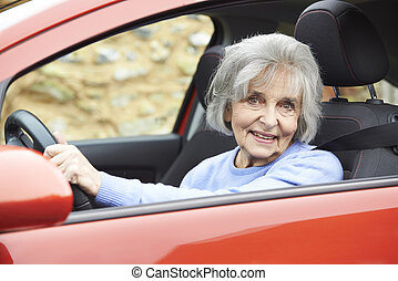 Portrait Of Smiling Senior Woman Driving Car