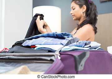 Woman packing suitcase - Closeup portrait, young woman...