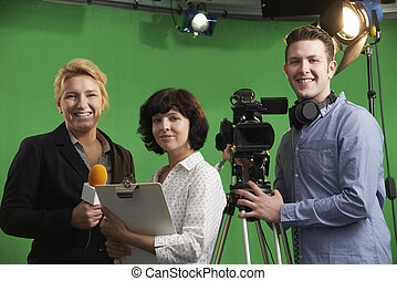 Portrait Of Cameraman With Presenter And Floor Manager In...