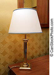 Lamp with a lamp-shade on a table