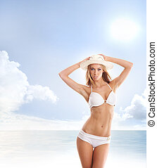 Young attractive girl in sexy swimsuit over sea and sky...