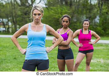 3 Girls Enjoying The Park - Three young women exercising at...