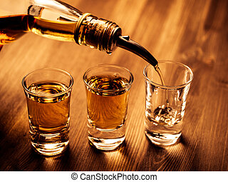 Filling glasses - Three shot glasses being filled with a...