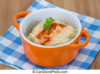 Hummus in the bowl with paprica and cedar nut