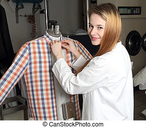 Woman in a dry cleaning on Ironing doll machine - A Woman in...