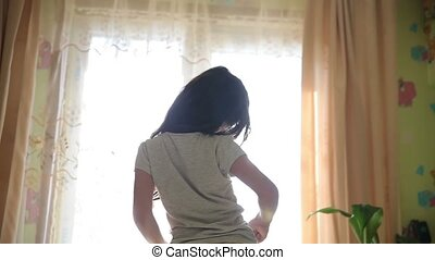 Teen girl stretches awake standing at window silhouette spin...