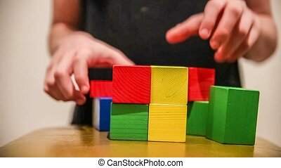 teenager boy builds a tower of bricks blocks play a major...