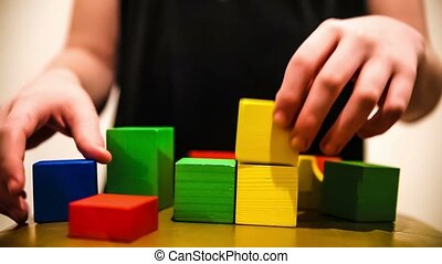 teenager boy builds tower of bricks blocks play a major hand...