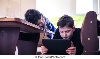 children boy and girl teens playing in the tablet online...