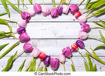 Heart of fresh tulips arranged on white wooden background
