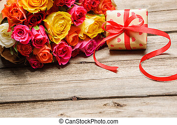 Bunch of roses with a gift box
