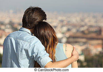 Couple dating in love and hugging watching the city - Back...