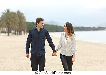 Couple in love taking a walk on the beach - Front view of a...