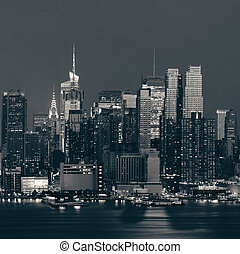 Midtown Manhattan skyline at dusk with street over Hudson...