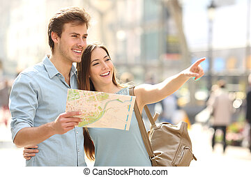 Couple of tourists consulting a city guide searching...