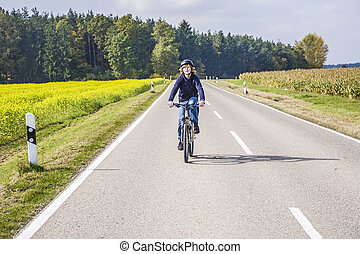 young in rural area - young boy on tour with the bike in...