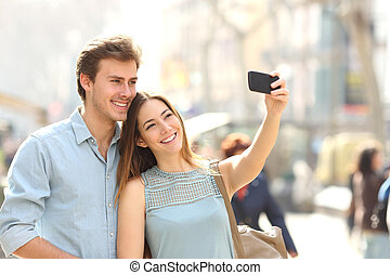 Couple of tourists photographing a selfie in a city street -...