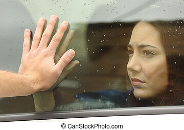 Couple saying goodbye before car travel holding hands...