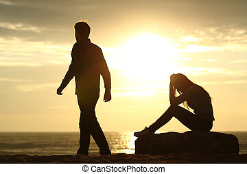 Couple silhouette breaking up a relation on the beach at...