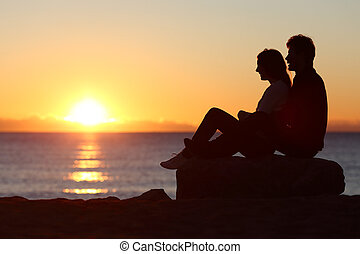 Couple silhouette sitting watching sun at sunset - Side view...
