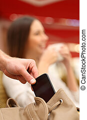 Thief stealing a mobile phone from a woman bag - Thief hand...