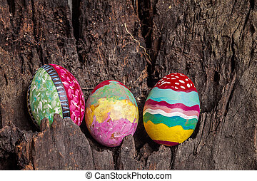 Colorfull easter egg with old brown log