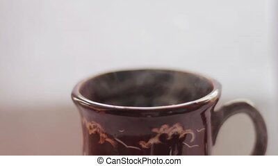 Pouring hot water into the mug, white background, close up,...