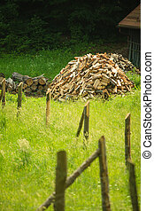 pile of wood behind wooden fence on a green grass - pile of...